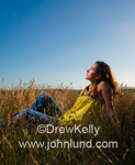 A woman sitting in a field of grain looking up at the sky and perhaps pondering her future existence.